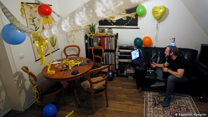 An adult having a video conference with birthday party decoration hanging in the room