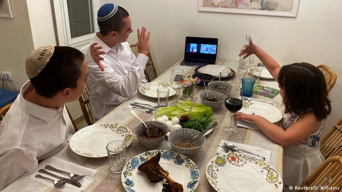 Three siblings in Israel wave to their grandmother as she joins their Passover Seder via Zoom