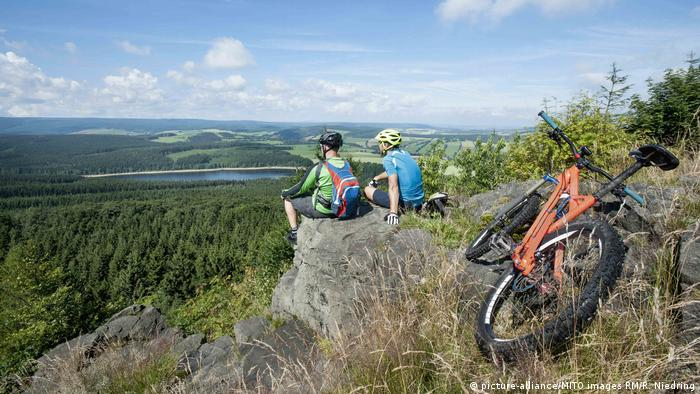 Cyclists sitting on a rock looking out over a valley in the Erzgebirge mountains, Chemnitz, Germany (picture-alliance/MITO images RM/R. Niedring)