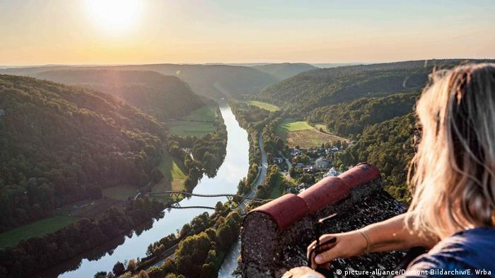A woman looking out from a castle ruin high vantage point at a river and hilly woodlands in Altmühl Valley, Germany