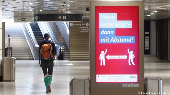 Cartel iluminado en Múnich, Alemania, que indica que se debe mantener distancia al caminar en espacios públicos.