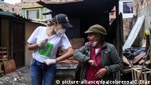 06.04.2020, Kolumbien, Bogota: «Merce» (l), eine junge Youtuberin, grüßt mit dem Ellenbogen eine Frau in einem ärmeren Viertel. «Merce» und ihr Team fahren durch die Stadt und versuchen Menschen, die im Alltag vom Müll-Recyceln leben, zu helfen. Über soziale Netzwerke hat «Merce» zu einer Spende für diese Menschen aufgerufen, da sie momentan aufgrund der von der Regierung verhängten Ausgangssperre keinen Lebensunterhalt haben. Im Kampf gegen das Coronavirus hat die Regierung die Bevölkerung dazu aufgerufen, bis zum 12. April nicht aus dem Haus zu gehen. Die Aktion der Youtuberin heißt «Liebe recyceln». Foto: Camila Diaz/colprensa/dpa +++ dpa-Bildfunk +++  
