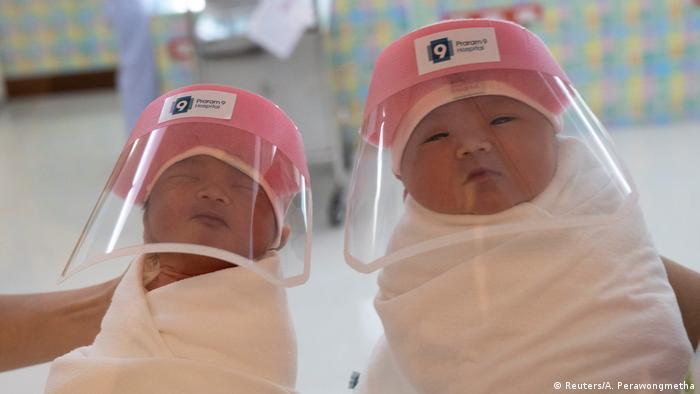 Foto simbólica de dos bebés recién nacidas con máscaras protectoras contra el COVID-19
