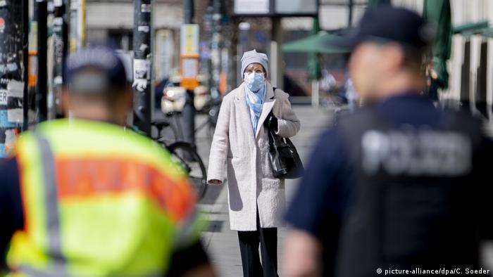 Mulher com máscara entre policiais em Berlim, na Alemanha