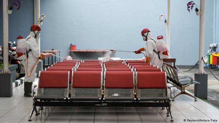 Indonesia's red cross personnel wearing protective suits spray disinfectant to prevent the spread of coronavirus disease