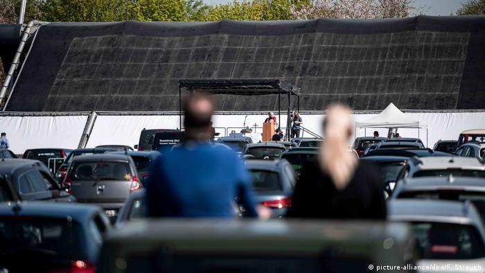 Ostergottesdienst im Autokino: Paarschaut aus dem Autodach auf Bühne und Pfarrer