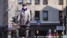 Eine Seniorin auf der Breite Straße posiert mit Atemschutzmaske. Köln, 03.04.2020   Verwendung weltweit