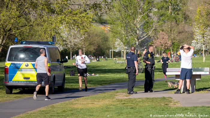 German police talks to people in a park