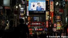 FILE PHOTO: A large screen on a building shows Japan's Prime Minister Shinzo Abe declaring a state of emergency, at Tokyo's famous entertainment district Kabukicho, following the coronavirus disease (COVID-19) outbreak, in Tokyo, Japan April 7, 2020. REUTERS/Naoki Ogura/File Photo