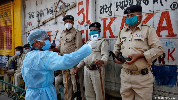 Indien | Coronavirus: Sanitäter misst Temperatur von Polizeiheinheiten in Ahmedabad (Reuters/A. Dave)