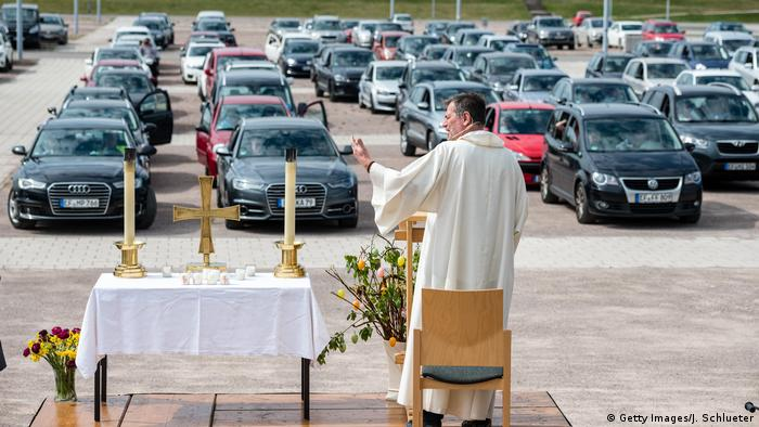 A German priest gives a sermon to people sat in their cars