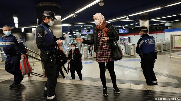 Police in Spain are seen handing out face masks to people at metro and train stations