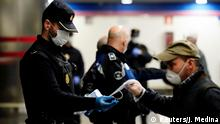A police officer gives out free protective face masks at a metro station during the lockdown amid the coronavirus disease (COVID-19) outbreak in Madrid, Spain, April 13, 2020. REUTERS/Juan Medina