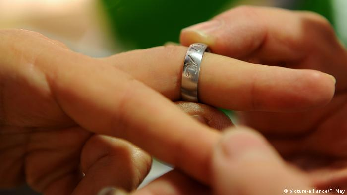A wedding band being put on a person's finger