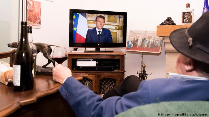 A confined French man in watching on television the speech of the French President Emmanuel Macron