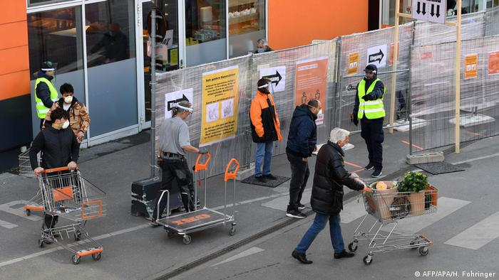 Shoppers wearing masks stand outside a store in Vienna