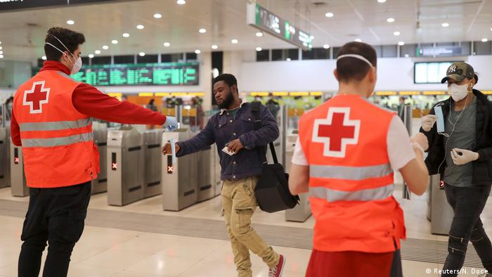 In Barcelona Red Cross workers hand out masks to public transport users