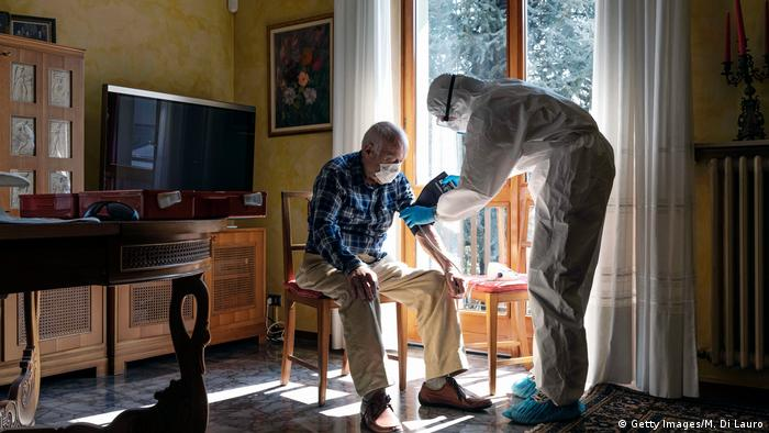 A member of the Italian Red Cross visits a patient at home in Bergamo, Italy