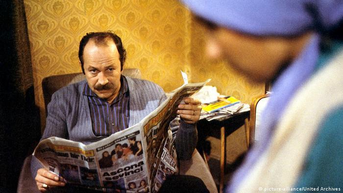 Filmstill 40qm Deutschland (picture-alliance/United Archives) türkischstämmiger Mann liest Zeitung, im Vordergrund eine Frau