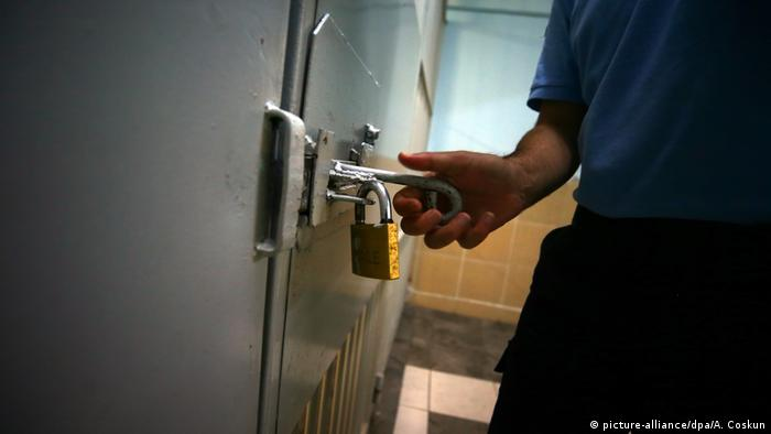 A hand holds a lock in a Turkish prison