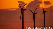 14.04.2020, Mecklenburg-Vorpommern, Brüsewitz: Windräder drehen sich vor dem von der aufgehenden Sonne orangerot gefärbten Morgenhimmel. In Norddeutschland beginnt der Tag mit Temperaturen unter null Grad. Foto: Jens Büttner/dpa-Zentralbild/dpa +++ dpa-Bildfunk +++ | Verwendung weltweit