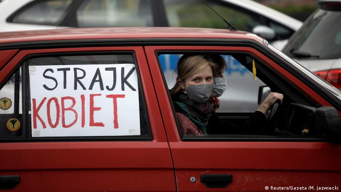 Women drive their car with a Women's Strike banner in protest