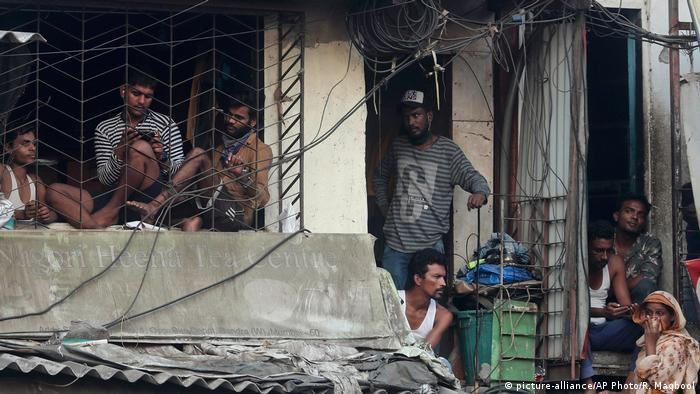 Indian migrant workers look out from a house after a protest against the extension of an ongoing lockdown in Mumbai