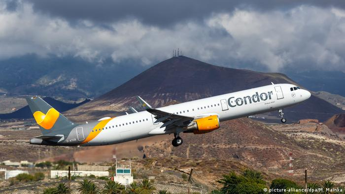 Condor plane taking off with a mountain in the distance