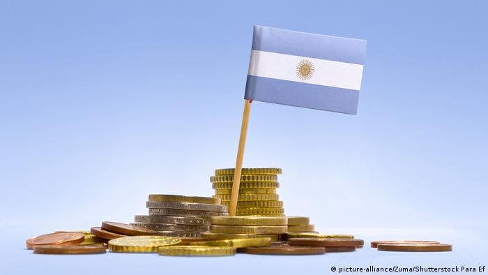 La bandera argentina, sobre monedas doradas y de cobre, símbolo de la deuda argentina.