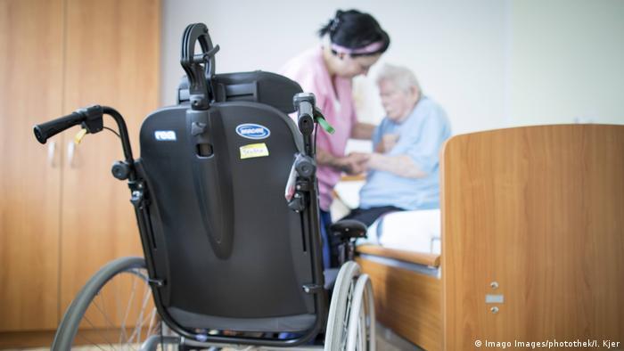 Altenpflegerin hilft Seniorin im Pflegeheim