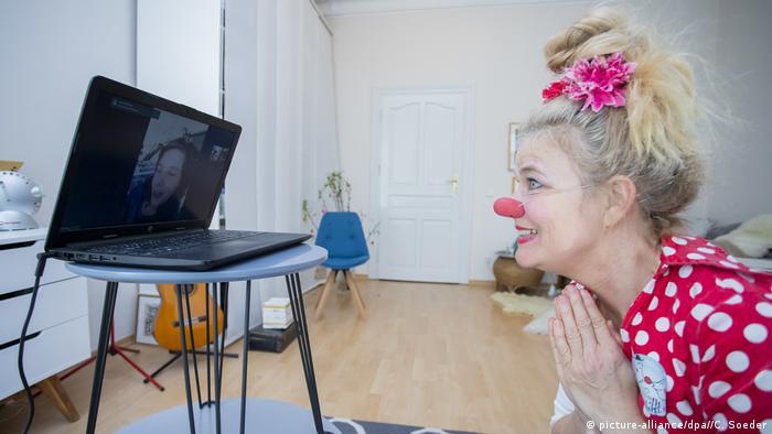 En la mayoría de los hospitales alemanes no se permiten visitas durante las restricciones a causa del coronavirus. Por eso, los payasos que se dedican a alegrar la estadía de los pacientes, especialmente de los más pequeños, deben realizar su actividad a través de internet. En la foto, la payasa Vitamina (Ute von Koerber), conversa con Pauline, de once años, internada en una clínica de Cottbus.