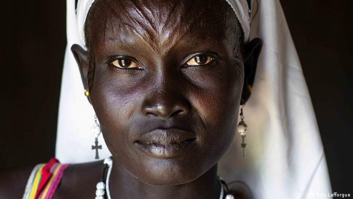 A close-up of a Mundari woman showing the scarification marks on her forehead.