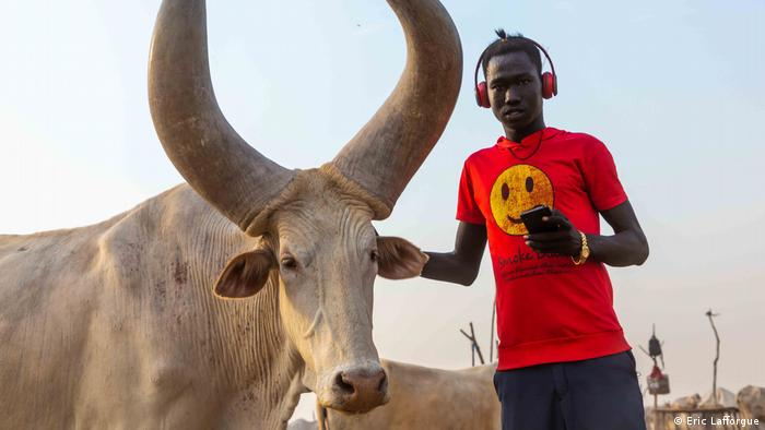 A Mundari man dressed in modern clothing and wearing headphones next to a cow.
