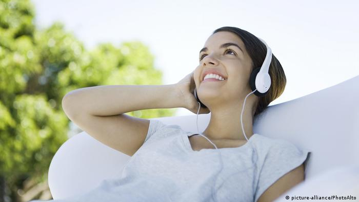 A woman listens to music through headphones