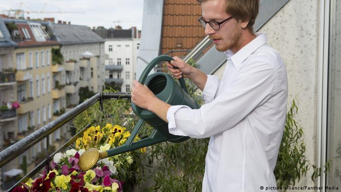 A man waters flowers on his balcony with a watering can