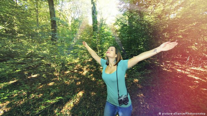 A woman walks in the woods with her arms outstretched