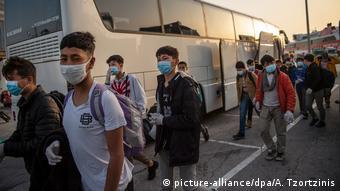 Несовершеннолетние беженцы в респираторных масках, призванных защитить их от заражения коронавирусом, из лагерей на границе Турции и Греции отправляются на автобусах в Люксембург и Германию