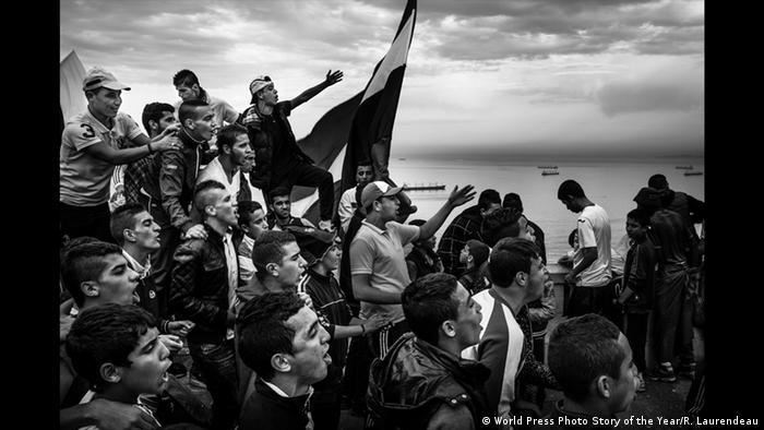 Young men shouting and gesticulating, the sea in the background and the Algerian flag. (World Press Photo Story of the Year/R. Laurendeau)