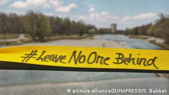 A yellow ribbon reads 'Leave no one behind' (picture-alliance/ZUMAPRESS/S. Babbar)