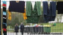 ARCHIV - 29.09.2014, Nordrhein-Westfalen, Hagen/Burbach: Sicherheitskräfte (hinten) laufen auf dem Gelände des Flüchtlingsheim der ehemaligen Siegerland-Kaserne während Wäsche zum Trocknen über einem Zaun hängt. Der seit zehn Monaten laufende Mammutprozess um misshandelte Flüchtlinge in einer Notunterkunft in Burbach verläuft zäh. (zu dpa: «Skandal um misshandelte Flüchtlinge in Burbach: Prozess verläuft zäh» vom 20.08.2019) Foto: Ina Fassbender/dpa +++ dpa-Bildfunk +++ | Verwendung weltweit