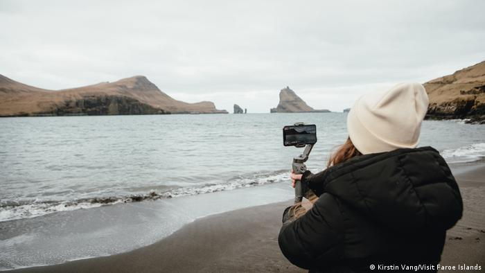 Sarah Jacobsen holds an iPhone up to capture the view at a Faroe Islands beach