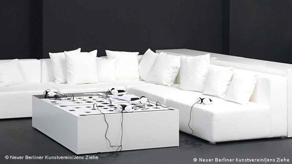 Диваны и стол с разъемами для наушников. Стол - маленькая модель выставочного пространства.