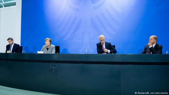 Angela Merkel sits at a press conference table with other German leaders