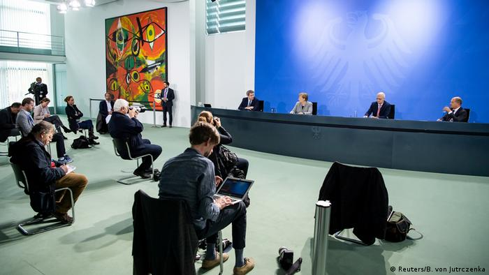 Reporters listen to Angela Merkel and other German politicians during a press conference on the coronavirus (Reuters/B. von Jutrczenka)