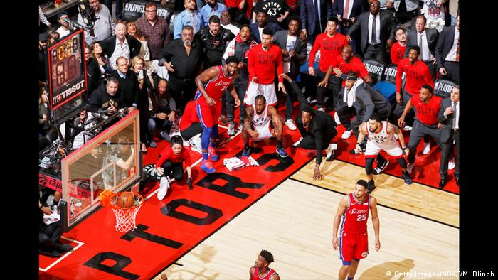 Basketball players in red watch open-mouthed as a ball goes into the basket while players in white look triumphant. (Mark Blinch, Getty Images/NBAE/M. Blinch)