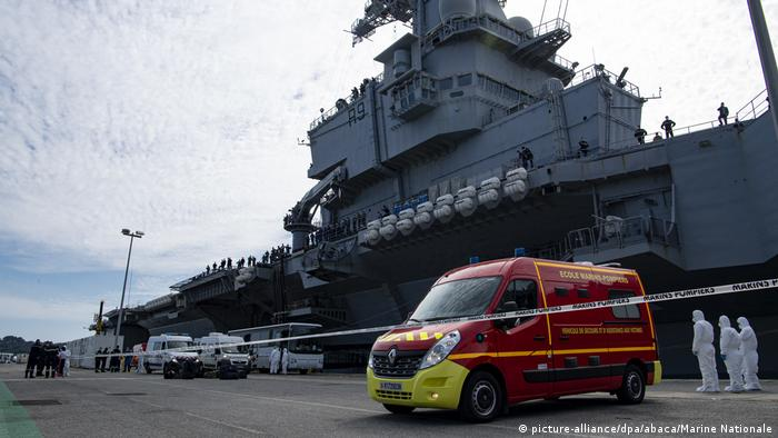 Hand out photo of emergency vehicles in front of the French aircraft carrier Charles de Gaulle as arriving in the southern French port of Toulon on April 12, 2020 with sailors onboard infected with COVID-19 (novel coronavirus).