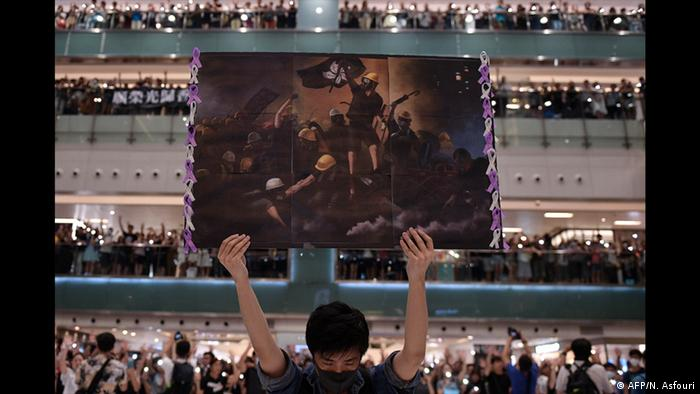A young man holds a poster over his bowed head, surrounded by a crowd.(AFP/N. Asfouri)