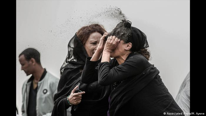 A woman in black with a veil has her hands in her face as another woman tries to console her (Associated Press/M. Ayene)