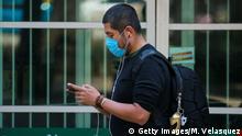 Mexiko Mann mit Handy und Gesichtsmaske Coronakrise