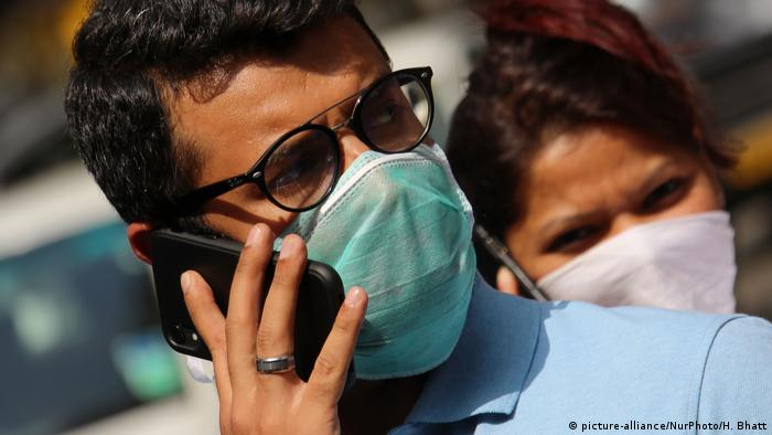 A man and a woman wearing face masks talk on mobile phones
